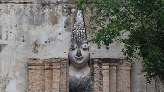 Một vị Phật khổng lồ nhìn qua một khoảng trống trong căn phòng chật hẹp, tạo nên vẻ động đáo riêng cho bức tượng.